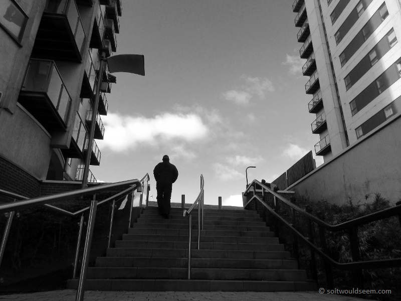 I'll Be Back - a man walks up steps in between blocks of flats in the Green Quarter of Manchester